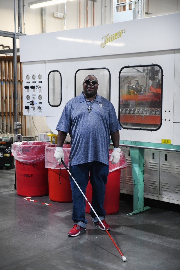 Jay Browder standing in his workplace holding his white cane