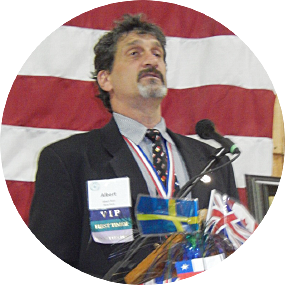 Albert Rizzi at a podium speaking before a thousand people