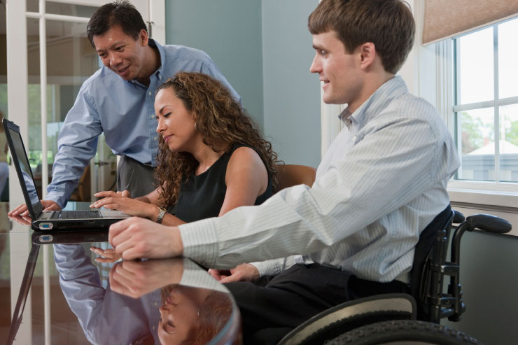 Businessman with spinal cord injury and a visually impaired Hispanic businesswoman using a laptop in an office