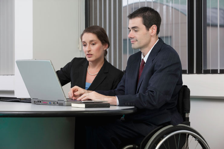 Attorney with spinal cord injury working on a laptop with a businesswoman