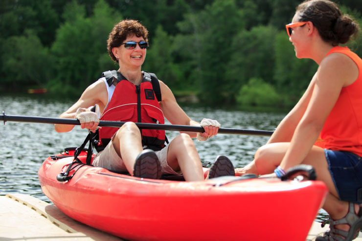 Instructor helping a visually-impaired woman with a Spinal Cord Injury with using a kayak