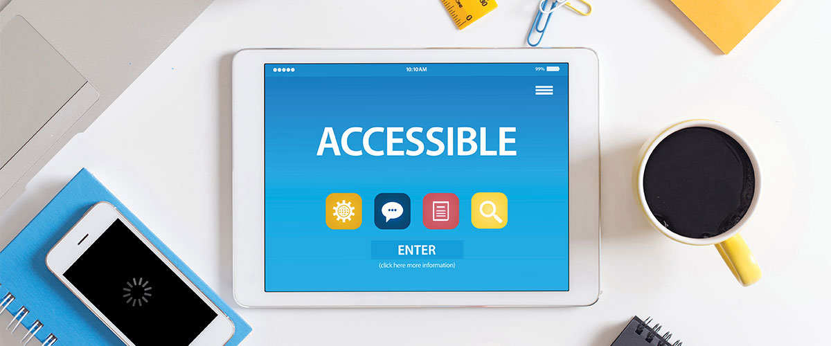 Accessibility Concept on a tablet PC on a desk with notebooks, laptop, desk items and a cup of coffee nearby