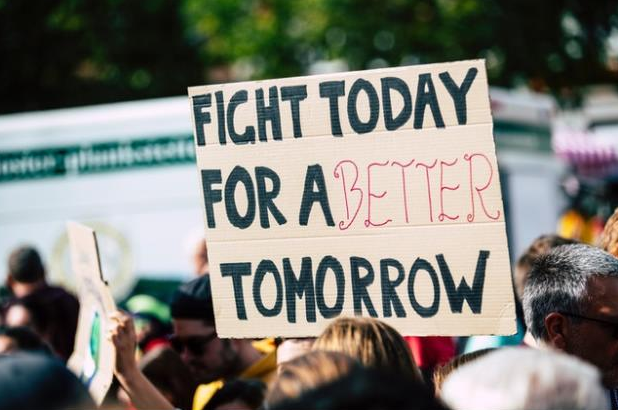 "A cardboard sing in front of a crowd that reads: ""Fight Today for a Better Tomorrow."""
