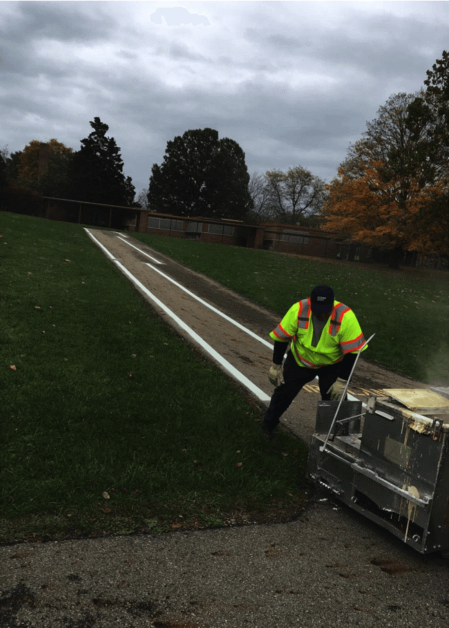 A man installing smart paint on a walkway of a campus