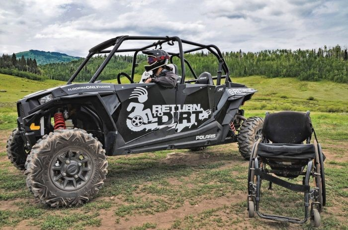 A man sitting in an off-road vehicle wearing a helmet with a wheelchair in the foreground.