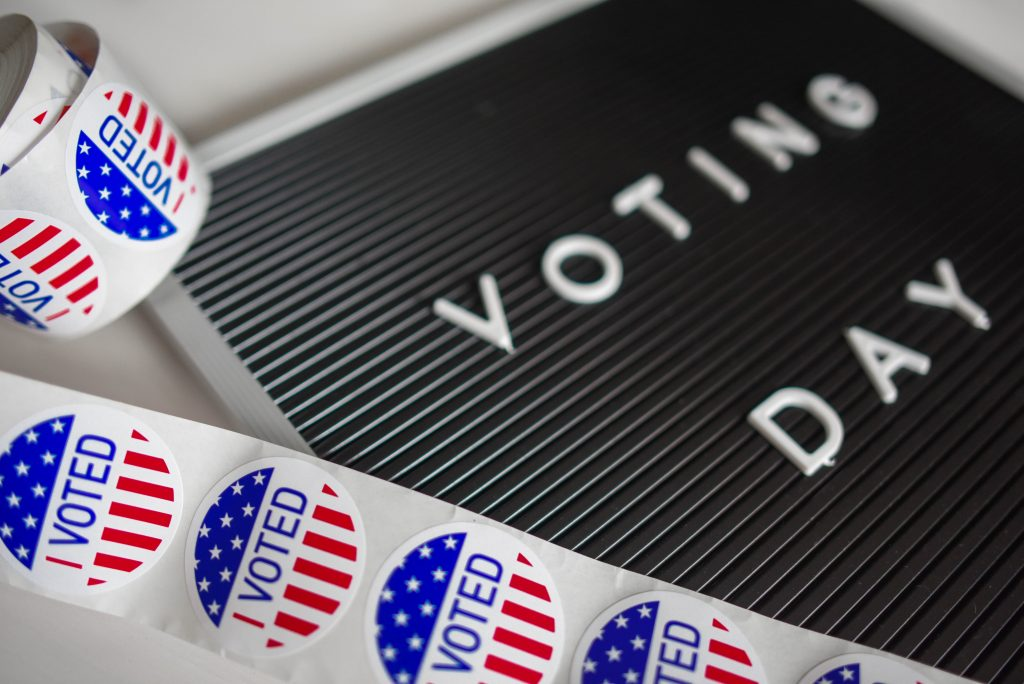 "Sign which says ""Voting Day"" and a roll of stickers which read ""I voted"" in the style of the American Flag"