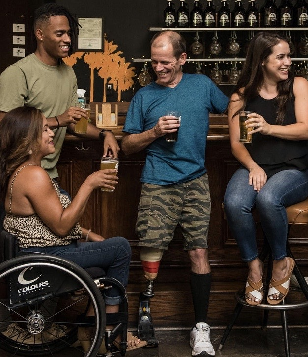 Color photo of four people of mixed races and genders celebrating at a bar. One is in a wheelchair; one has an artificial leg. They are all smiling.