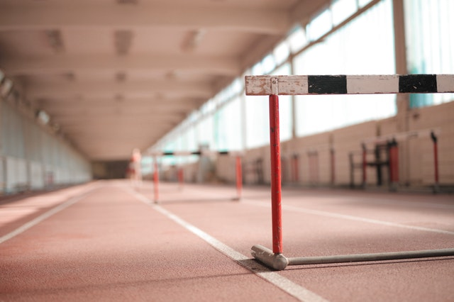 A running track. One lane is clear, and the other lane has hurdles.