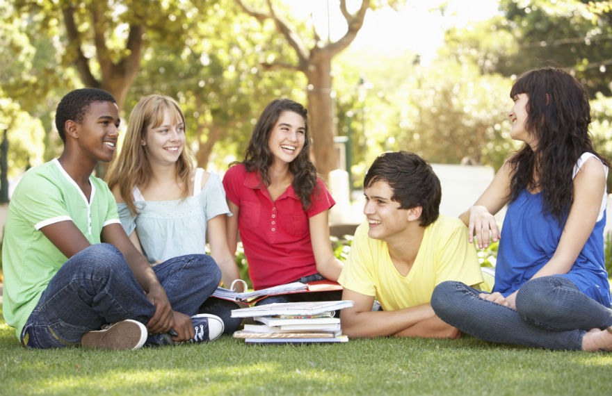 Five students sitting on the lawn and smiling with books open